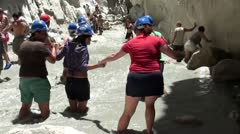 Group of tourists passing mountain torrent Stock Footage