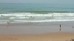Surfers beach, pan shot, slow motion Stock Footage