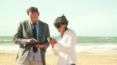 Businesspeople with tablet computer and cellphone by the sea HD - stock footage