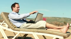 Businessman finishing work on laptop and relaxing on sunbed HD Stock Footage