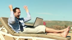 Successful, excited businessman with laptop lying on sunbed HD - stock footage