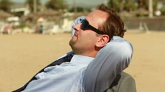 Businessman relaxing on sunbed on the beach, steadicam shot HD Stock Footage