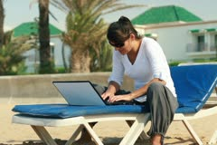 Woman with laptop sitting on sunbed on the beach NTSC Stock Footage
