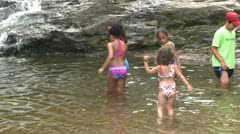 Children wading in the water at the bottom of a waterfall Stock Footage