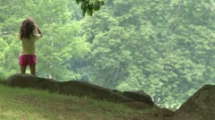 Little girl standing on a hill looking at the woods - stock footage