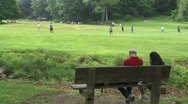 Stock Video Footage of Two people sitting on a bench in a Nature Reserve watching boys play ball