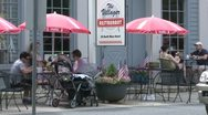 People eating under market umbrellas at a sidewalk cafe (1 of 3) Stock Footage