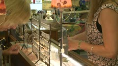 Woman looking at jewelry at a boutique Stock Footage
