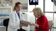 Stock Video Footage of Doctor showing her patient her chart