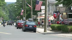 Cars parked along the street with flags on the telephone poles Stock Footage