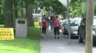 Stock Video Footage of Two woman walking by a sign for a sidewalk festival