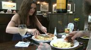 Heavily tattooed man eating a sandwich with a woman eating pizza at restaurant Stock Footage