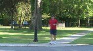 Stock Video Footage of Man jogging across street (1 of 1)