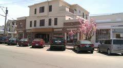 Looking across Main Street with pink blossoms along the sidewalk (1 of 2) Stock Footage