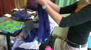 Stock Video Footage of A store clerk folding up sweaters on a display