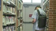 Stock Video Footage of A student looking for a CD in the library