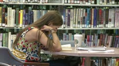 A young girl with Starbucks coffee studying in the library Stock Footage