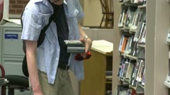 Student looking at DVR's in the library Stock Footage