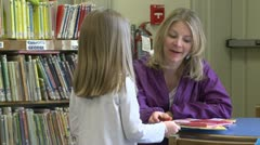 A child getting books for her mother to read to her (2 of 3) Stock Footage
