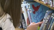 Stock Video Footage of Little girl looking through rows of children's books (3 of 4)