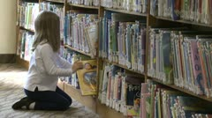Little girl looking through rows of children's books (4 of 4) Stock Footage