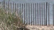 Stock Video Footage of A sand dune with a wooden fence with the ocean in the background