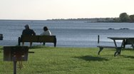 Stock Video Footage of A couple sitting on a bench in a picnic area by the ocean (1 of 2)