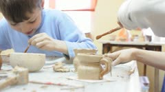 group of children brushing their pottery - stock footage