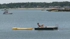 Woman sunbathing on a raft with a rubber dinghy tied to it (1 of 2) Stock Footage