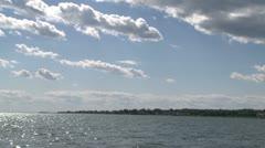 Ocean water glistening below puffy clouds Stock Footage