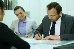 Real estate agents signing contract and giving keys to female client - stock footage
