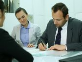 Real estate agents signing contract and giving keys to female client Stock Footage