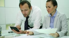 Business couple making calculations using a calculator Stock Footage