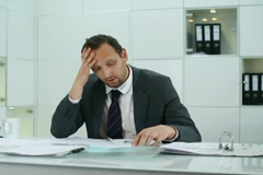 Businessman overwhelmed by too much paperwork Stock Footage
