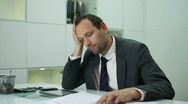 Worried businessman sitting at office desk with tablet and paperwork Stock Footage