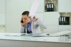 Angry businesswoman with cellphone  in the office - stock footage