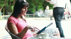 Young woman with tablet drinking tea in bar, outdoors - stock footage