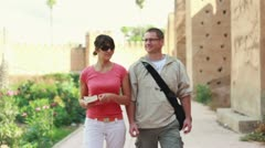 Happy tourist couple with guidebook sightseeing ancient walls Stock Footage