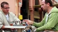 Two male friends talking and drinking tea in the city Stock Footage
