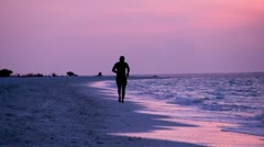 Sports jog along the beach at sunset Stock Footage