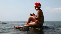 Woman on the beach in santa hat calls on the phone 2 - stock footage