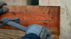 A carpenter fix a nail with his hammer - stock footage