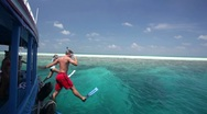 Snorklers jumping from boat Stock Footage