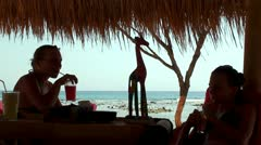 Girls at the open air bar on the shore of Ocean Stock Footage