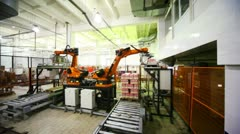 Hydraulic crane automatically takes from conveyor and places packages of bottles Stock Footage