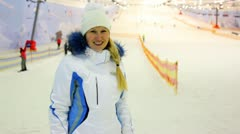Blonde nice girl gestures shows her delight in indoor ski Stock Footage