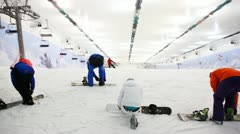 Professional sportsmans with snowboard prepares for training in indoor ski Stock Footage