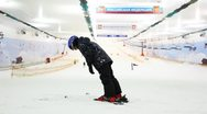 Little skier boy holds balance and does some exercises on top of hill in sport Stock Footage