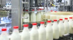 Stock Video Footage of fresh milk poured into bottles, screwed red caps and send to consumers