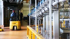 Small forklift goes near conveyor inside dairy factory Stock Footage